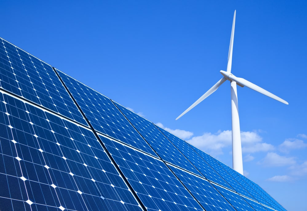 Wind turbine and solar panels in front of blue sky