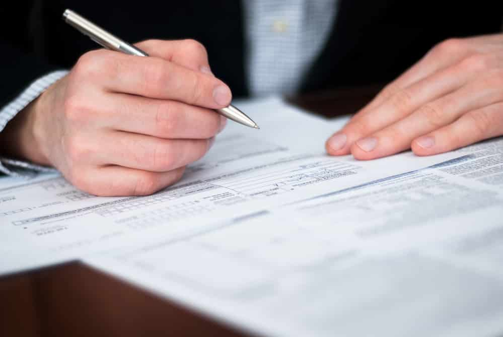 Close-up of businessman's hands filling out forms