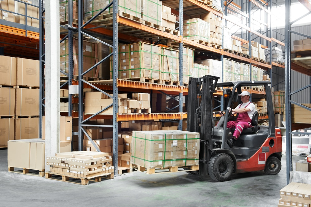 Forklift operator in manufacturing facility, moving boxes