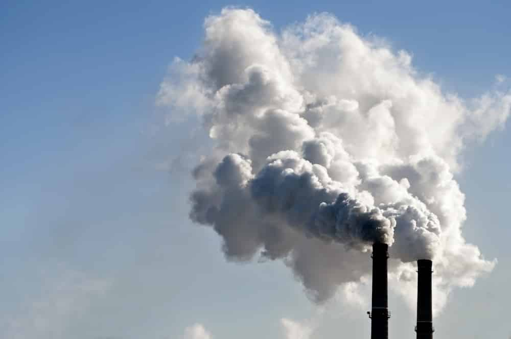 Close-up of factory chimneys emitting pollution into blue sky